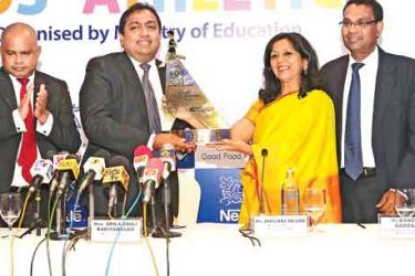 Nestle Lanka PLC Managing Director Shivani Hegde handing over the winner's trophy of the inaugural National Kids Athletics Competition to Education Minister Akhila Viraj Kariyawasam. Also in the picture are Special Advisor to the Education Ministry on Sports, Sunil Jayaweera (left extreme), Education Ministry secretary Sunil Hettiarachchi (2nd from left), Nestle Lanka Vice President Bandula Egodage (2nd from right) and Education Ministry's Project Officer Milroy Jayamanne. Picture by Shan Rambukwella