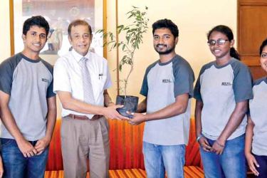 Chairman of the People's Bank Chairman Hemasiri Fernando  hands over a 'goodwill plant' to the students of the University of  Colombo, to be planted at the University of Jaffna.