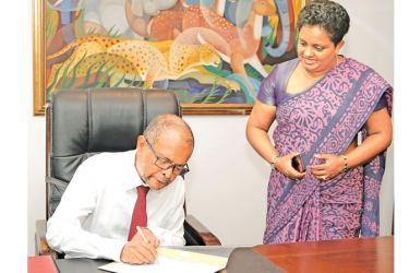 Nimal Tillekeratne, CEO of Pan Asia Bank signing the first official document.