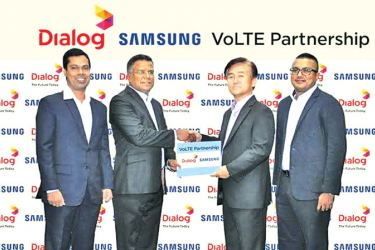 Dialog Axiata's Group Chief Technology, Pradeep De Almeida (2L) hands over the VoLTE partnership agreement to Youngmin Shin, Managing Director of Samsung Sri Lanka (2R). Also in the picture are Asanga Priyadarshana, Head of Mobile Business of Dialog Axiata (L), and Nigel Adams, Head of Marketing for Samsung Sri Lanka.