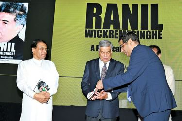 The launch of the book 'Ranil Wickremesinghe-A Political Biography,'was held at the BMICH yesterday. Here, the writer Dinesh Weerakkody presenting a copy of the book to Prime Minister Ranil Wickremesinghe as President Maithripala Sirisena and Speaker Karu Jayasuriya look on.  Picture by Malan Karunaratne