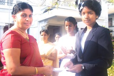 Principal of Mahamaya College, Indra Withanachchi presenting a cash award to Samidhi Manthilani Munasinghe who came island 2nd in the 2016 G.C.E.(O/L) examination.