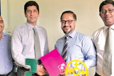 Shiraz Lye, Director Sales and Marketing South Asia - IFS handing over the agreement to Pawan Tejwani, Managing Director of Cable Solutions Lanka, as Mithila Ranjithan, Principal Consultant IFS South Asia and Priyanka Irugalbandara, Director Quality Floors Lanka looks on.