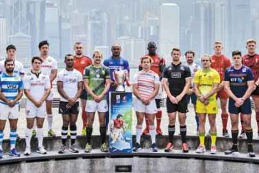Captains of teams competing in the annual Hong Kong Rugby Sevens pose with the winner's trophy (C) in front of a view of skyline of Hong Kong on April 5, 2017, during a promotional event ahead of the tournament. AFP