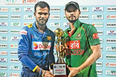 The two captains Upul Tharanga and Mashrafe Mortaza share the series trophy after Bangladesh won the second T20I to draw level at one-all. AFP