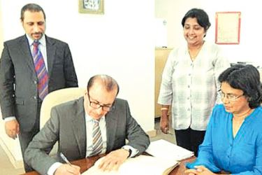 UAE Ambassador signs the Visitors' book of the Chamber, while the CEO of the Chamber and Lilakshini De Mel, Senior Assistant Secretary General look on.