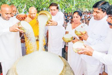 President Maithripala Sirisena and Agriculture Minister Duminda Dissanayake along with others offering the first share of rice from the Maha harvest to the Bodhi.