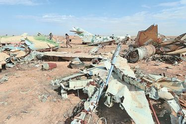 A Syrian Democratic Forces (SDF) fighter walks near destroyed airplane parts inside Tabqa military airport after taking control of it from Islamic State fighters, west of Raqqa city on Saturday. - AFP