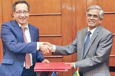 Secretary to the Ministry of Finance, Dr. R. H. S. Samaratunge exchanging the agreement on behalf of the Government with Ambassador to Sri Lanka and the Maldives for the Delegation of the European Union, Tung Lai Margue.
