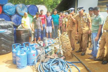 The Police officers inspecting the seized equipment and barrels of goda