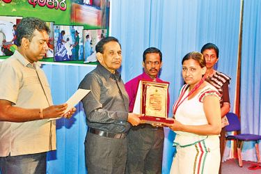 Health Minister Dr. Rajitha Senaratne hands over an award to a recipient while others look on.