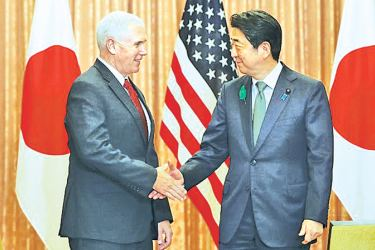 US Vice President Mike Pence greeted by Japanese Prime Minister Shinzo Abe during their meeting at Abe's official residence in Tokyo yesterday. - AFP