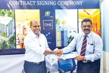 DAMAS Company  Managing Director Abdulla Salih and Walkers CML Group Executive Vice President Lal Perera exchange agreements.