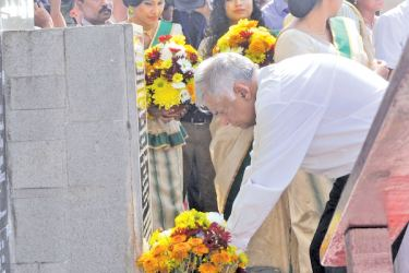 lacing flowers in tribute to the late President  R. Premadasa at his statute in Hulftsdorp yesterday.