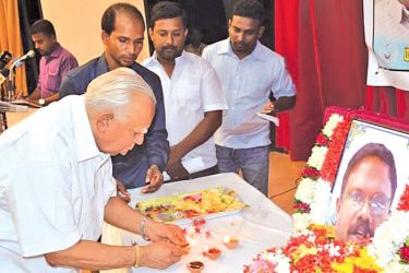 Opposition Leader R. Sampanthan lighting a lamp at the photograph of late Sivaram