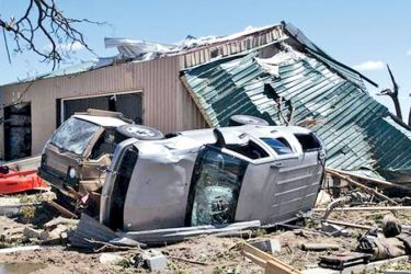 An overturned vehicle rests on the ground surrounded by debris in Canton, Texas.