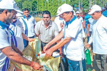 President Maithripala Sirisena joining in the cleaning activities at Getambe, Kandy playground where the  SLFP May Day rally was held on Monday.