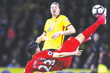 Liverpool's German midfielder Emre Can connects with this overhead kick to open the scoring in the English Premier League football match between Watford and Liverpool at Vicarage Road Stadium. AFP