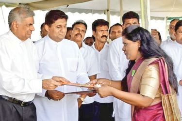 Prime Minister Ranil Wickremesinghe distributing deeds. Housing Construction Minister Sajith Premadasa and National Housing Development Authority Chairman L. S. Palansooriya also participated.