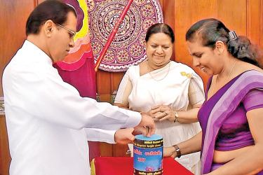 President Maithripala Sirisena is seen making a contribution to the proceeds collected through flag sales after the pinning of the first Ranaviru flag. Picture courtesy President's Media Divison