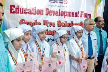 Several students in Ampara who excelled in the Grade 5 exam along with officials and parents.