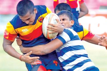 Trinity winger Rashan Bandaranayake (ball in hand) is held by Josephian lock forward Kelaniyagoda in their Singer 'A' division inter-schools league rugby match played at Havelock Park yesterday. (pix by Susantha  Wijegunasekera).