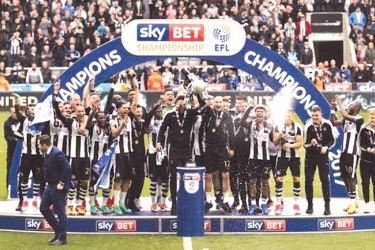 Newcastle celebrate winning the league with the trophy.