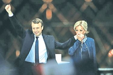 French President elect Emmanuel Macron and his wife Brigitte Trogneux celebrate on the stage at his victory rally near the Louvre in Paris.- AFP
