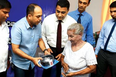 Colombo District  MP,  S.M. Marikkar  and Director  Sales and Marketing and Corporate Affairs Chaminda Ediriwickrama, handing over a regulator to a victim.