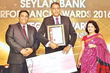 Manager Galle Branch Chamli Kulawardane with respective achievement credential and cash award flanked by Director and CEO of Seylan Bank Kapila Ariyarathne and  Senior Independent Director Seylan Bank  Coralie Pietersz.