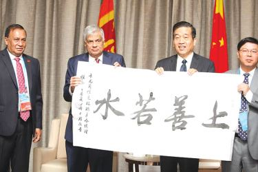 Prime Miniter Ranil Wickremesinghe being presented with a memento containing traditional Chinese letters by the Chines e Book Publishers Association representatives.