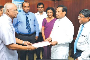 Prof. Tuley De Silva handing over the report to Health Minister Dr. Rajitha Senaratne while Acting Director General of Health Services Dr. Jayasundara Bandara and others look on.
