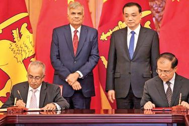 Prime Minister Ranil Wickremesinghe and Chinese Prime Minister Le Keqiang observing the signing of an agreement for a Chinese grant of 400 million Yuan in Beijing by China's Deputy Minister of Trade Fu Ziying and Sri Lanka's Minister of Development Strategies and International Trade Malik Samarawickrama.