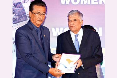 SAARC Chamber of Commerce and Industry President Surai Vaidya  handing over the SAARC Investment Outlook to Prime Minister Ranil Wickramasinghe at the Women Leadership Summit 2017. Pictures by Kelum Liyange