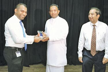The Chairman Of YSP Navin Perera presenting a token of appreciation to the Minister of Petroleum and Petroleum Gas Chandima Weerakkody along with CASA Secretary General Dhammika Walgampaya.