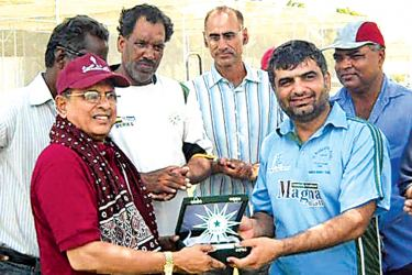 Dr. Upali Mahanama (in red T-shirt) during an official visit to Pakistan where he was presented with a traditional Ajrak and souvenir by the Pakistan Disabled Cricket Association.