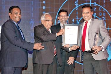 HNB Chief Digital Officer Sidath Wijeratne, accepting the award from, former Chairman of LankaClear Sarath Silva, LankaClear General Manager and CEO Channa de Silva and, Former General Manager and CEO of LankaClear Sunimal Weerasooriya is also in picture.