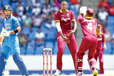 West Indies' captain Jason Holder (C) looks on as wicketkeeper Shai Hope (R) takes a catch to dismiss India's captain Virat Kohli (L) during the fourth One Day International (ODI) match between West Indies and India at the Sir Vivian Richards Cricket Ground in St. John's, Antigua, on July 2. AFP