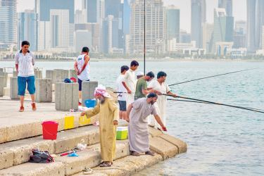 People fishing from Corniche, with West Bay in background. Doha, Qatar. - AFP