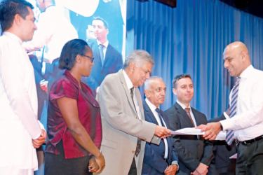 Prime Minister Ranil Wickremesinghe awarding a letter of appointment to one the heads of the Task Force, Director General of the Securities and Exchange Commission, Vajira Wijegunawardane. Picture by Shan Rambukwella
