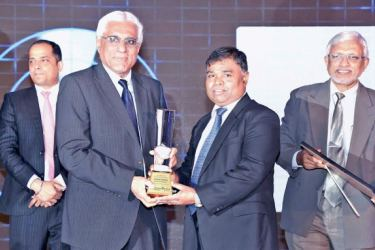 BoC General Manager D.M. Gunasekeara receiving the Gold Award for the Overall Winner at the LankaPay's Technovation Awards 2017 from Central Bank Governor Indrajith Coomaraswamy