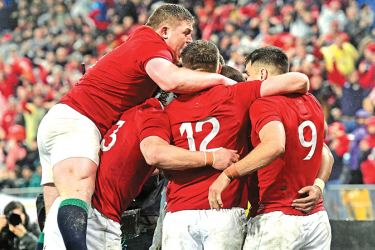British and Irish Lions' Tadhg Furlong (top L) jumps on his teammates as they celebrate a try during the second rugby union Test between the British and Irish Lions and the New Zealand All Blacks in Wellington on July 1.  AFP