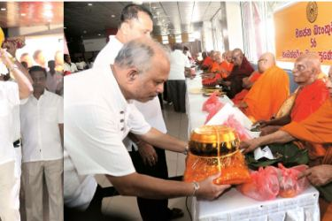 People's Bank Board of Directors  Jehan P. Amaratunga conveyed the sacred casket; CEO and GM  N. Vasantha Kumar offering alms to the Maha Sangha.