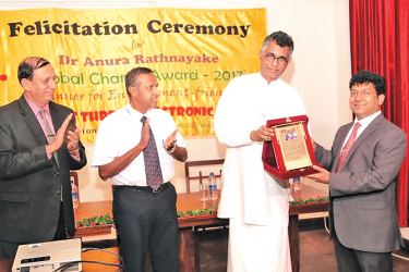 Megapolis and Western Development Minister Patali Champika Ranawaka handing over the award to Dr. Anura Ratnayake.  Picture by Tilak Perera.