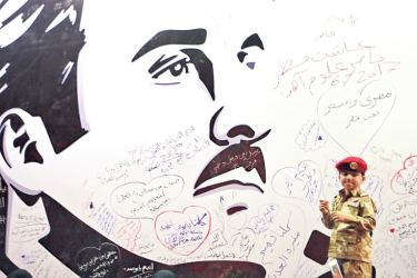 A young boy poses for a photo after writing a comment on a wall bearing a portrait of Qatar's Emir, Sheikh Tamim bin Hamad Al Thani, which has become the symbol of Qatari resistance during the month-long row between Doha and neighbouring countries, in Doha on Saturday. - AFP