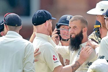 England's Moeen Ali (R) celebrates the wicket of South Africa's JP Duminy with teammates during the fourth day of the first Test match between England and South Africa at Lord's Cricket Ground in central London on July 9. AFP