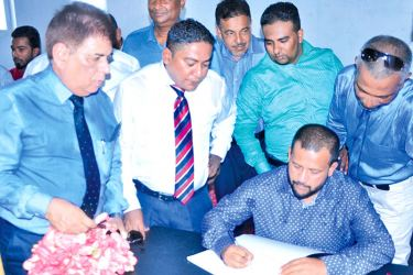 Having launched the Lanka Ashok Leyland East centre, Minister of Industry and Commerce Rishad Bathiudeen signs LAL East's guestbook joined by LAL Chairman Dr. Siraz Meerasahib (standing second from left) and CEO of LAL Umesh Gautam (standing far left) on 9 July in Sainthamaruthu.