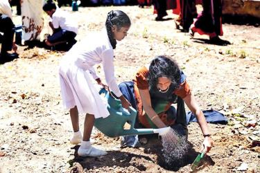 Priyanthi Chandrasekera, Project Manager - Scaling up Nutrition through a Multi-Sector Approach, FAO, plants a tree with a student of Wijerama Maha Vidyalaya