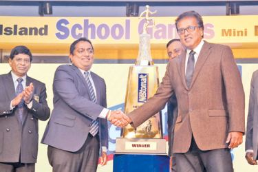 Education Minister Akila Viraj Kariyawasam shakes hand with Nestle Lanka vice president Norman Kannangara in front of Sri Lanka Schools Mini Marathon champion trophy during the press conference. Education Ministry Consultant (sports), Sunil Jayaweera and Nestle Lanka vice president Bandula Egodage are also present. Picture by Chinthaka Kumarasinghe