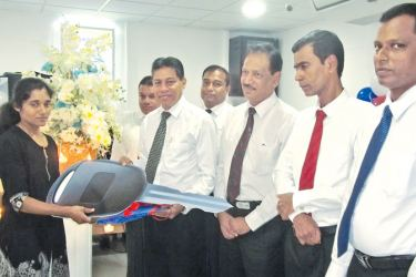 People's Leasing and Finance opened its 8th People's Leasing Service Centre at Ragama recently. Here the People's Leasing and Finance PLC Chief Executive Officer Sabry Lbrahim is seen handing over a Vehicle Ownership Certificate to a customer, R.A. Rukshika of Rajagiriya. Deputy General Manager Branch Operation, Layanal Fernando, Chief Managers Ranil Perera, Chamil Herath, Gampaha People's Bank Regional Manager D.V.K. Ratnayake, People's Leasing Kadawatha Branch Manager Tharakabellana and Ragama Service Ce